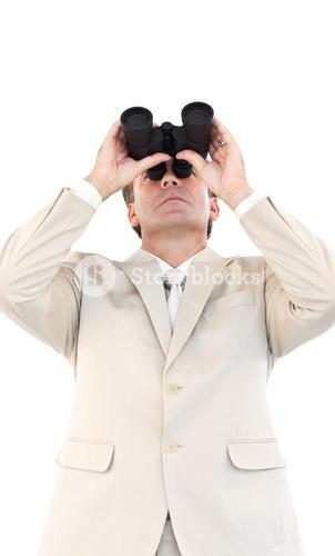 Serious businessman looking through binoculars in front of the camera