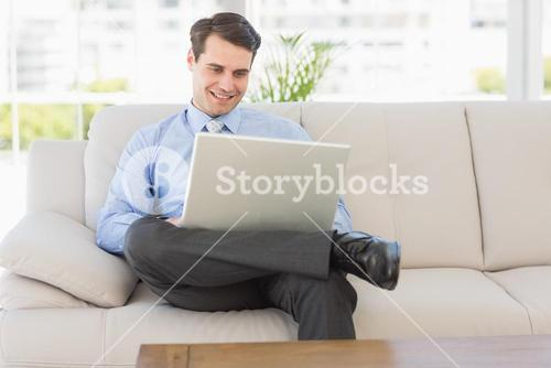 Businessman using laptop sitting on the couch