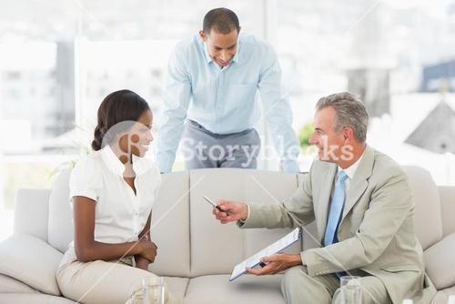 Salesman handing pen to client to sign the paperwork