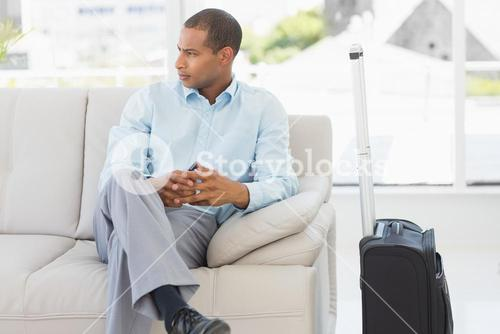 Businessman sitting on sofa waiting to depart on business trip