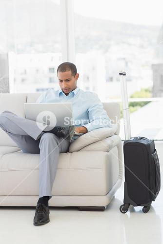 Businessman using laptop sitting on sofa waiting to depart on business trip
