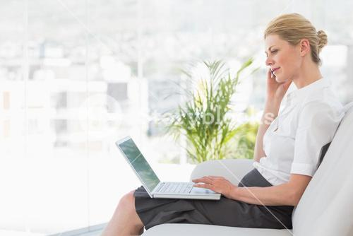 Businesswoman sitting on the sofa with laptop