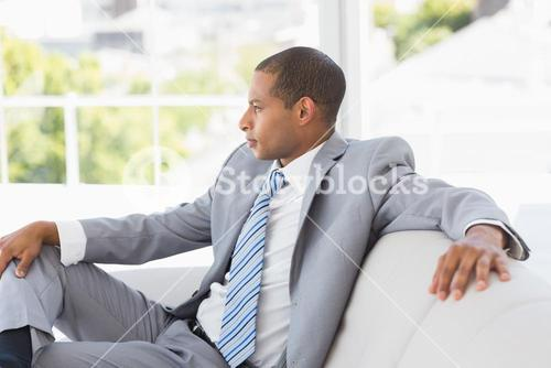Serious businessman thinking on couch