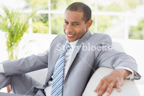Businessman sitting on couch smiling at camera