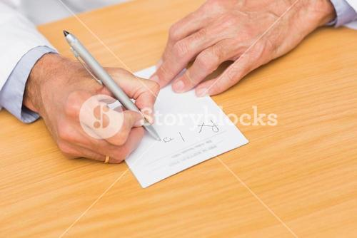 Doctor sitting at his desk writing on prescription pad