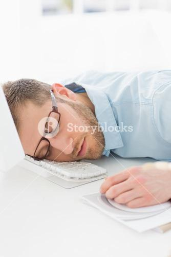 Exhausted designer sleeping at his desk
