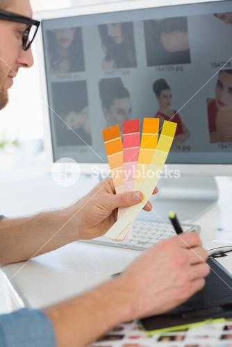 Handsome designer working with digitizer holding colour chart at his desk