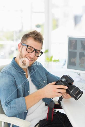 Photographer holding his camera and smiling at camera