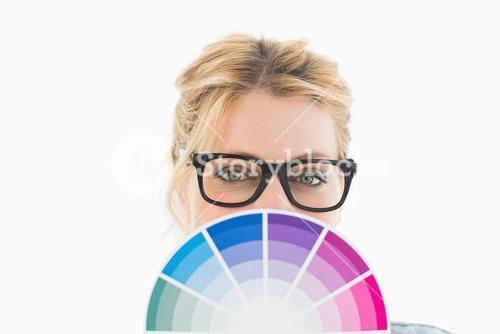 Blonde designer holding colour wheel