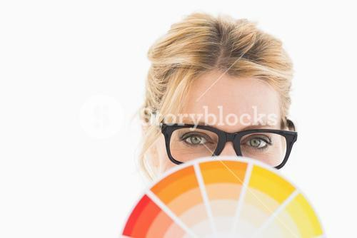 Blonde designer wearing glasses holding colour wheel