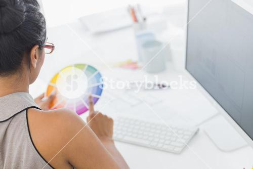 Designer working at her desk holding colour wheel