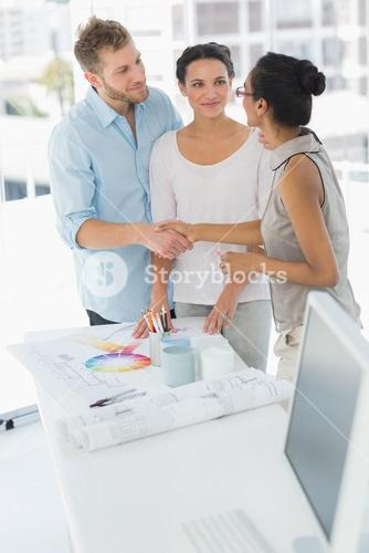 Interior designer shaking hands with happy client