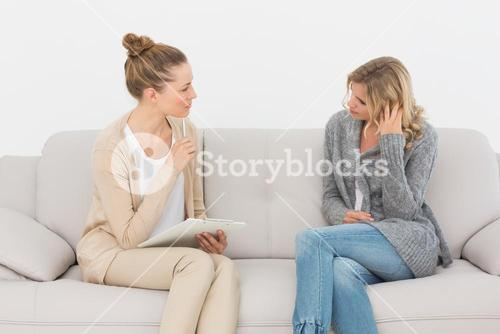 Upset woman talking to her therapist on the couch