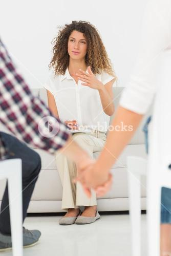 Therapist looking at reconciled couple holding hands