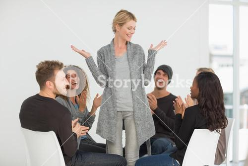 Rehab group applauding happy woman standing up