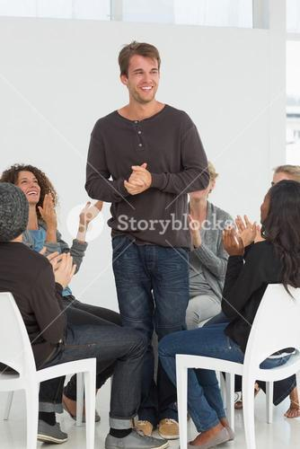 Rehab group applauding happy man standing up