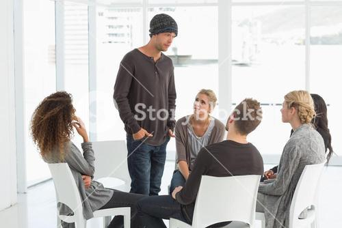 Rehab group listening to man standing up introducing himself