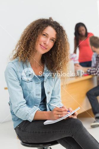 Thinking designer sitting in front of her colleagues using digital tablet