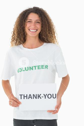 Smiling volunteer showing a thank you poster