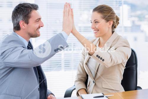 Colleagues giving high five in business meeting