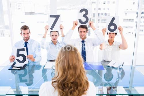 Group of panel judges holding score signs in front of woman