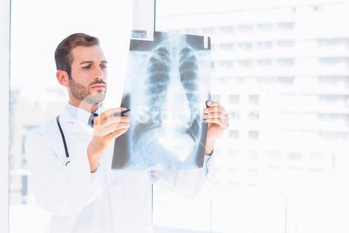 Male doctor examining xray in medical office