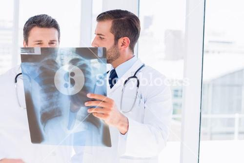Two male doctors examining xray