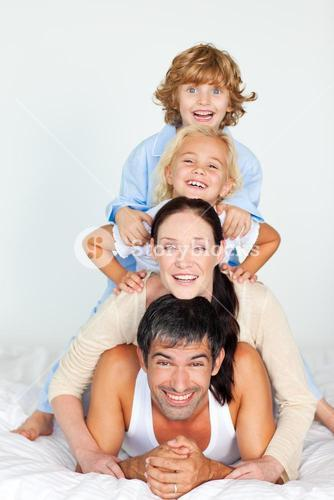 Parents and children playing in bed