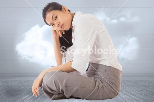 Composite image of businesswoman sitting cross legged leaning on hand