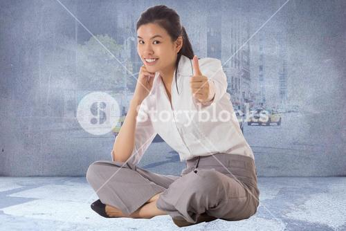 Composite image of businesswoman sitting cross legged showing thumb up