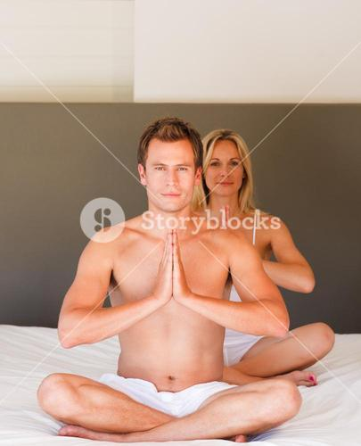 Couple doing exercises on bed