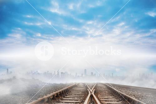 Train tracks leading to city on the horizon