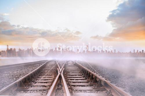 Train tracks leading to misty city