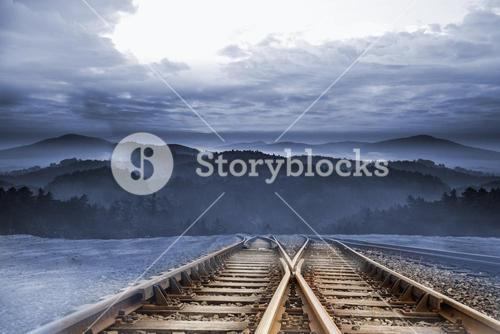 Train tracks leading to mountains