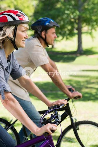 Couple riding bicycles in a park