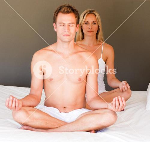 Young girl doing yoga on bed with her boyfriend