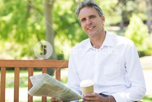 Businessman with disposable cup and newspaper in park