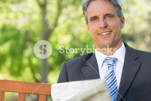 Businessman with newspaper in park