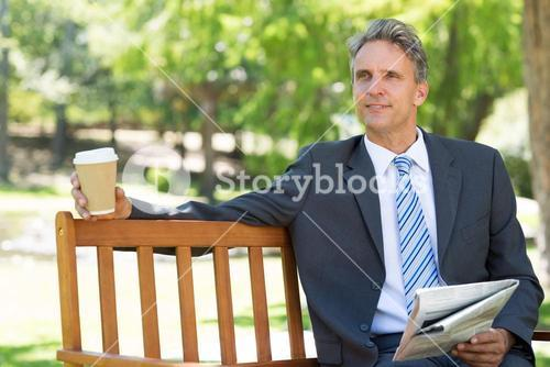 Thoughtful businessman with newspaper and coffee cup