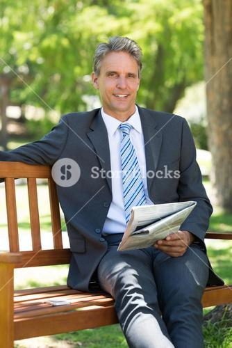 Businessman with newspaper sitting in park