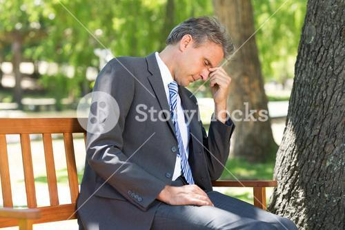 Depressed businessman in park