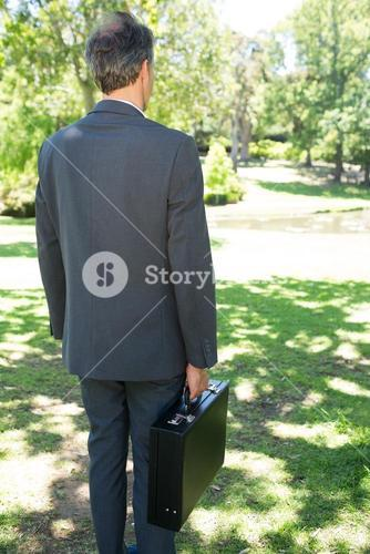 Businessman carrying briefcase in park