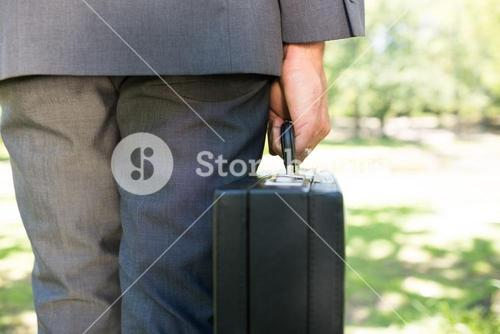 Midsection of businessman carrying briefcase