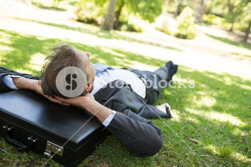 Businessman resting head on briefcase