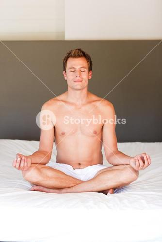 Young boy doing spiritual moves on bed