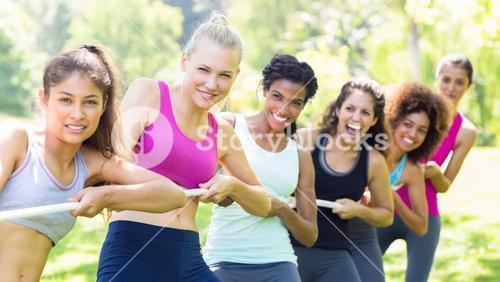 Women pulling a rope in park