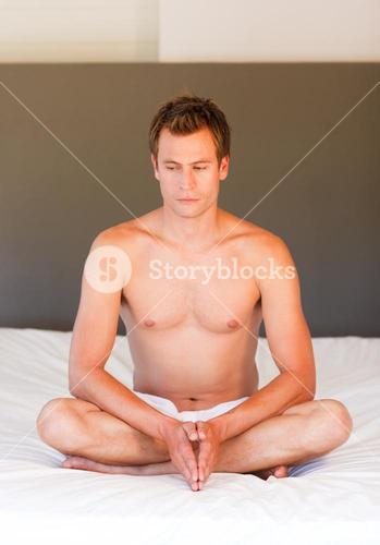 Young boy doing yoga moves on bed