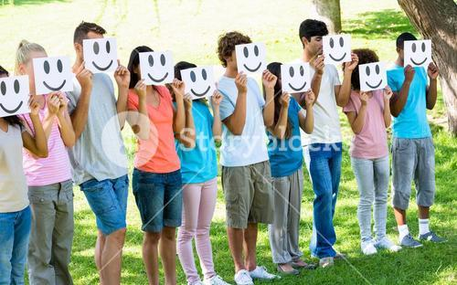 Friends holding smileys in front of faces