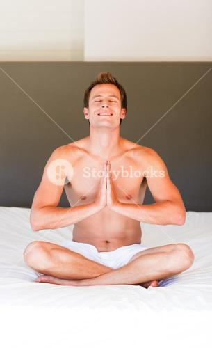 Attractive man meditating on bed
