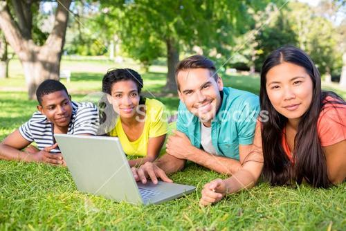 Smiling students with laptop on campus